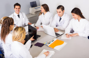 Multinational young interns and happy professor cooperating at hospital meeting